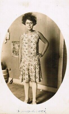 RPPC Young Woman with Unruly Hair in Patterned Dress Hand on Hip in Living Room