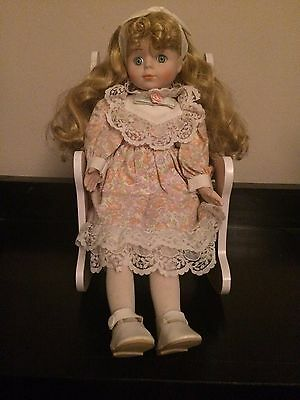 Blonde Porcelain Doll In Rocking Chair