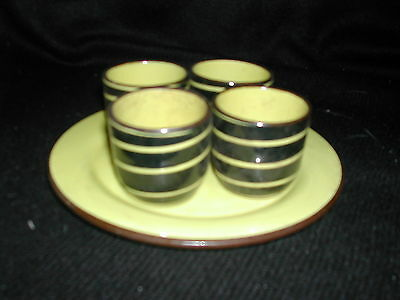 Set of 4 brown egg cups with yellow stripes on brown plate by Torquay Ware