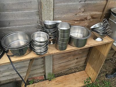 A variety of stainless steel gravy pots and containers