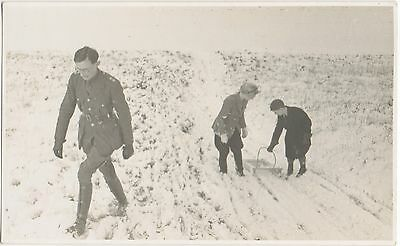 German Officer in uniform,lady & child with a sled on a snow covered hillside