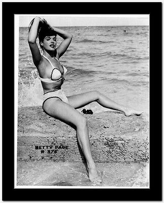 Bettie Page sitting in Swimsuit High Quality Photo