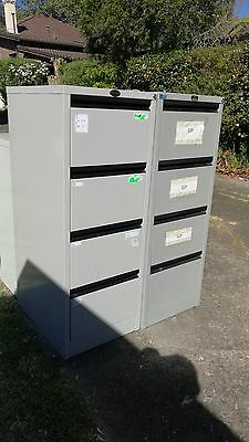 White metal filing cabinet with four drawers and a key