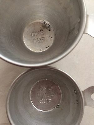 2 Vintage aluminum measuring cups, sizes stamped in letters on Bottom.