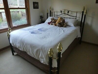 Queen brass bed complete with mattress base and mattress.