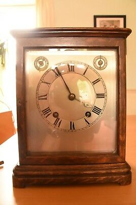 Oak cased mantle clock, unsigned silver dial, skeleton design with three windows