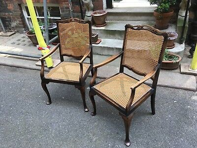 A pair of Edwardian mahogany and cane panelled gin chairs