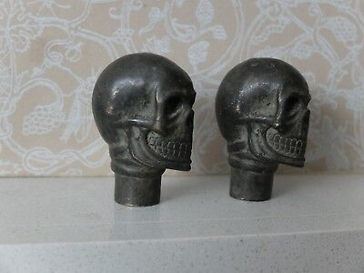 Two brass skull walking stick tops with patina