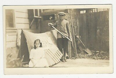 RPPC, Playacting small girl w/U.S. flag, boy with sword next to tent, 1910s-20s?