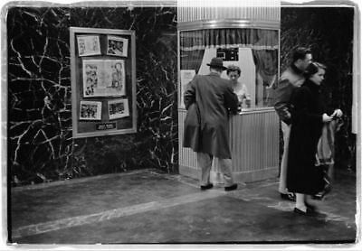 Man purchasing movie ticket,woman in ticket booth,couple,February 9,1958,Theater