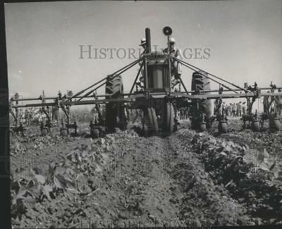 1967 Press Photo Two men ride a tractor equipped with a six row cultivator
