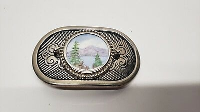 Belt buckle with lake and mountains.
