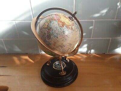 Stylish globe on metal stand with compass underneath