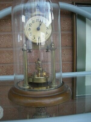 400 day clock with glass dome and a disk pendulum