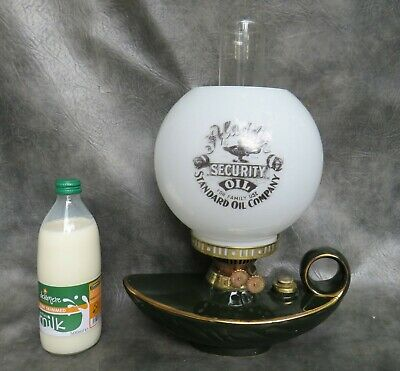 A Nice Ceramic Genie Shaped Oil Lamp With Aladdins Oil Advertisement Shade