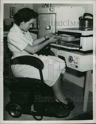 """1957 Press Photo Pat Mills rides in a """"Sley Ride"""" indoor electric chair"""