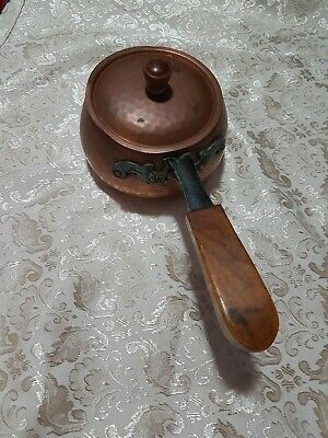 A  Copper Pot With A Metal  And Wooden Handle