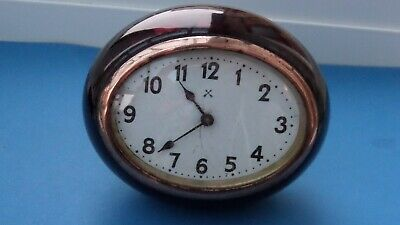 An Attractive Little Oval Vintage Clock set in a Deep Red Resin with White Face