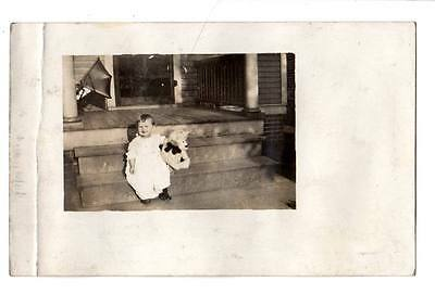 RPPC real photo cute smiling baby child steps teddy bear buggy in background