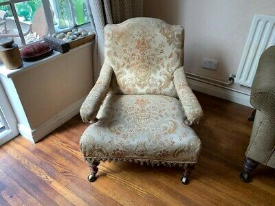 An Edwardian armchair with upholstered back and armrest.