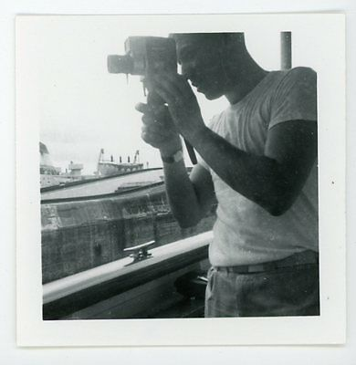Man in white t shirt looking in viewfinder of 8mm camera. Vintage snapshot photo