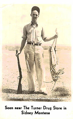 Exaggeration Postcard,Hunter with Giant Grasshopper,Sidney,Montana,1937