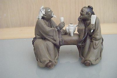 miniature chinese mud men figures sitting having a chat and tea.