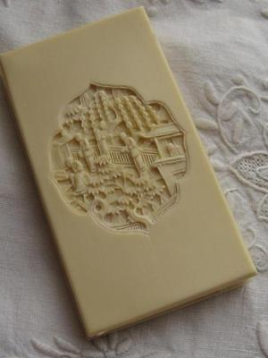 Chinese carved needlebook, classic scenes in cartouche on both sides, resin