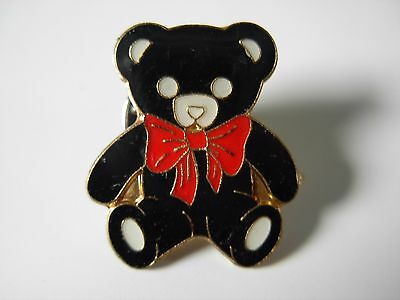 Teddy bear with red bow. Possible Charity pin badge.