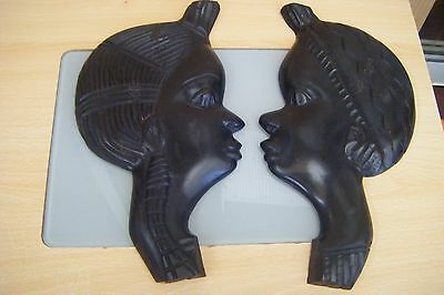 a pair of african carved wooden wall hangings