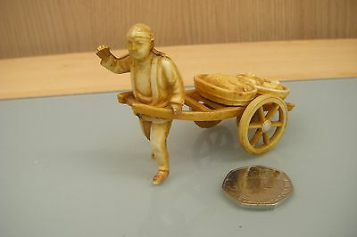 japanese celluloid figure of man pulling cart loaded with fish