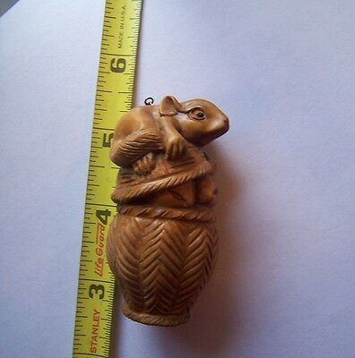 Carved wood netsuke squirrel on nut basket signed 2 3/4 inch