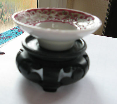 Small Pink Chinese Porcelain Shallow Bowl on a   dark wooden stand.