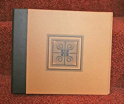 Three-ring binder / folder to hold CD / DVDs plus 10 refill pages. Pale brown.