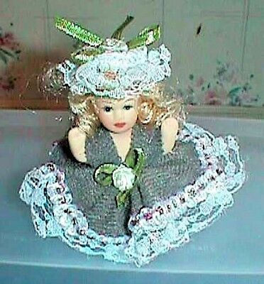 Miniature Porcelain Doll Sits 3 Inches Tall Wearing Dress and Hat With Lace Trim