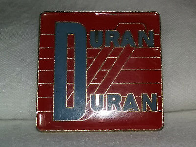Vintage Duran Duran Pin: heavy brass with curved glass front, 1.25 x 1.25 inches