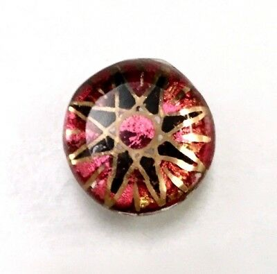 Small kaleidoscope button with a red, black and gold star center. Mint