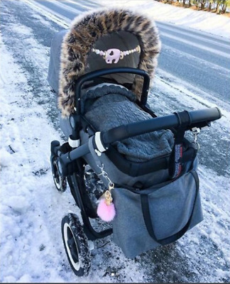 A cute winter sleeping bag knitted with a fur to a newborns baby carriage