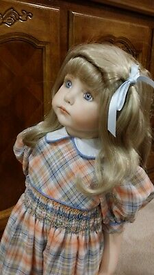 Porcelain doll in pretty smocked collotes. Blue shoes. 60cm hi. kept under glass