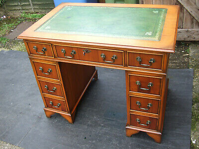 A small antique reproduction yew wood pedestal desk