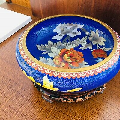 Large vibrant blue cloisonne bowl with red and cream flowers. Wooden stand.