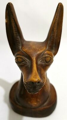 An ancient Egyptian statue in the shape of a cat, made of heavy stone material