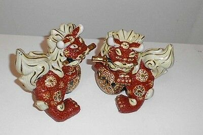 VINTAGE SET OF SMALL PORCELAIN CINNABAR FOO DOGS WITH SWORDS.