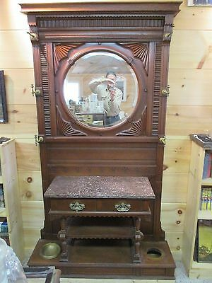 antique oak hall tree with round beveled mirror and marble top