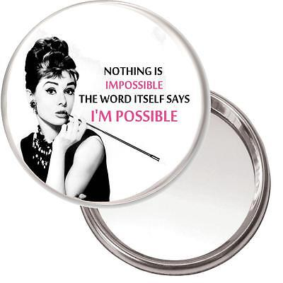 "Audrey Hepburn Makeup Mirror ""Nothing is Impossible..."" in a black organza bag."