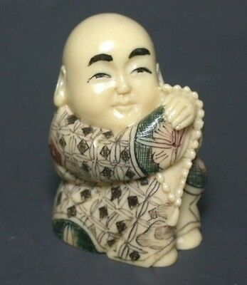 Japanese ivory colored bone netsuke - Boy Monk sits with Rosary Beads,signed