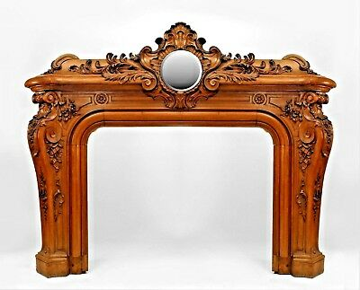 French Louis XV style walnut fireplace mantel with a circular mirrored panel abo