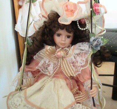 Collectible Porcelain Doll Dressed in Pink Sitting on Swing