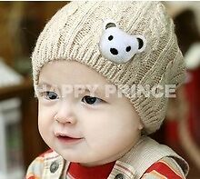 Childrens one size pull on twisted knitted cotton hat with bear motif .