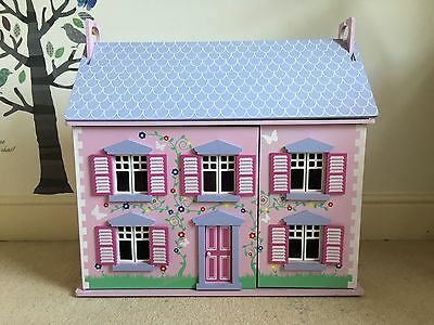 Wooden dollhouse with furniture and figures.